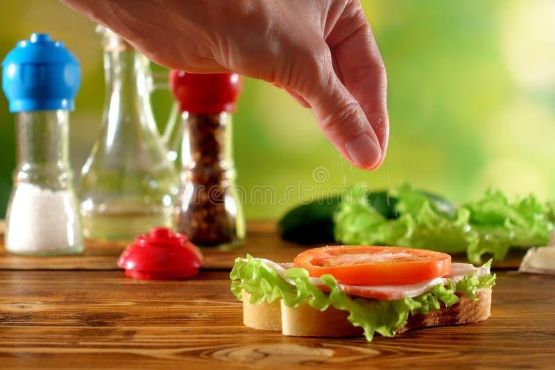 Женщина солит сандвич с томатом и салатом стоковая фотография