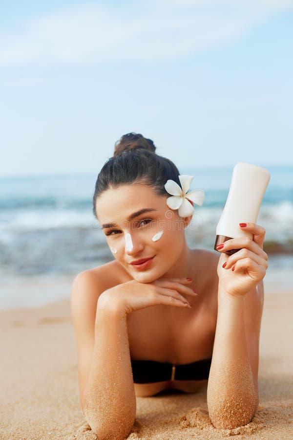 Женщина солнцезащитного крема прикладывая бутылку показа лосьона suntan Красивая усмехаясь счастливая женщина со сливк suntan леж стоковое фото