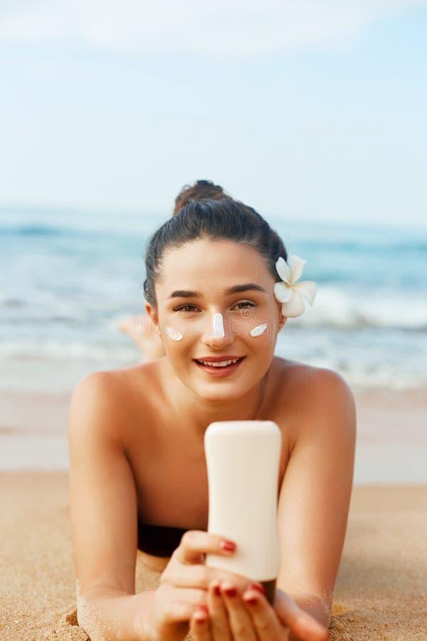 Женщина солнцезащитного крема прикладывая бутылку показа лосьона suntan Красивая усмехаясь счастливая женщина со сливк suntan леж стоковая фотография