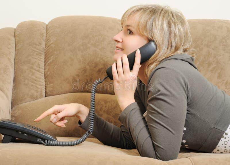 женщина софы телефона говоря стоковые изображения rf