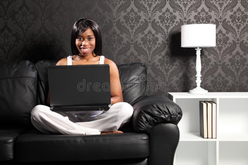 женщина софы черного счастливого интернета ся занимаясь серфингом стоковая фотография