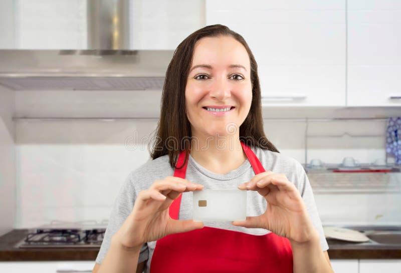 Женщина сохраняет с кредитной карточкой в отечественных расходах стоковое изображение rf