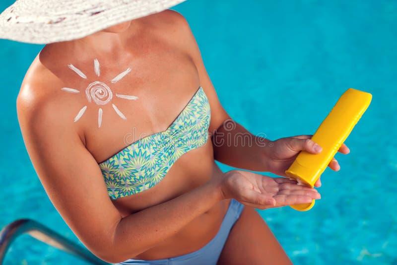 Женщина со сливк предохранения от солнца в форме солнца на ее людях груди, лете, празднике и концепции здравоохранения стоковое фото rf