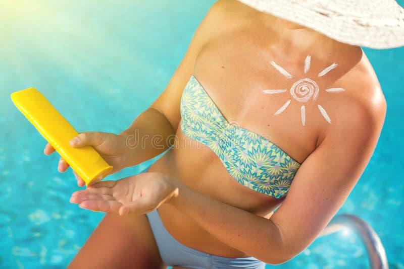 Женщина со сливк предохранения от солнца в форме солнца на ее людях груди, лете, празднике и концепции здравоохранения стоковое изображение