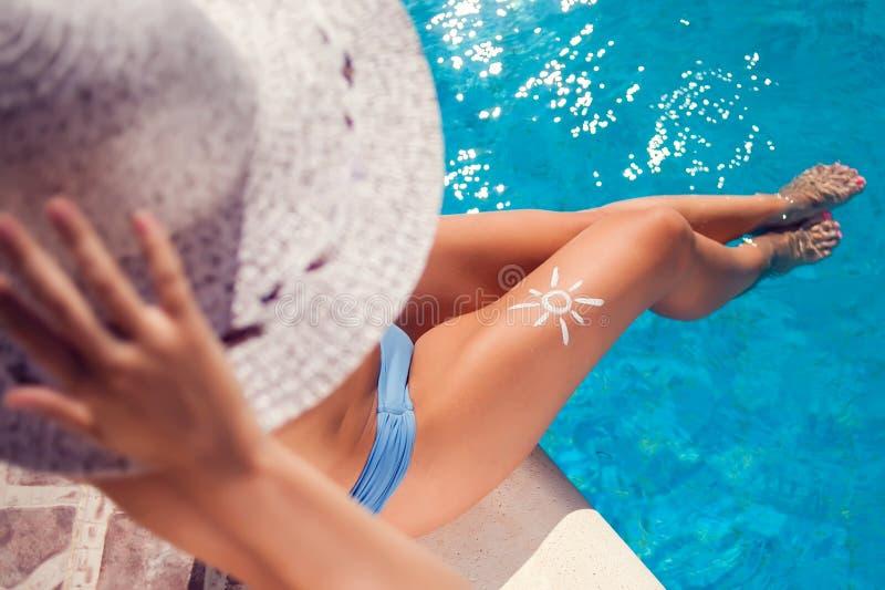 Женщина со сливк предохранения от солнца в форме солнца на ее ноге Люди, лето, праздник и концепция здравоохранения стоковые изображения