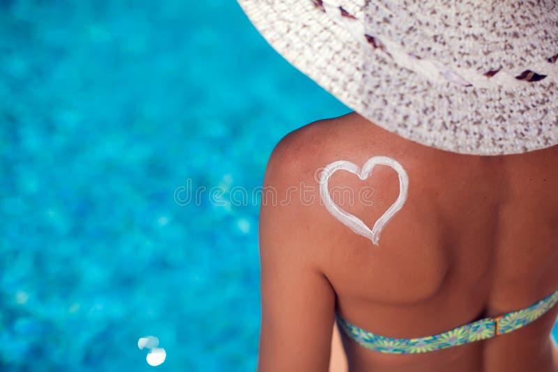 Женщина со сливк предохранения от солнца в форме сердца на ее плече Люди, лето, праздник и концепция здравоохранения стоковые изображения rf