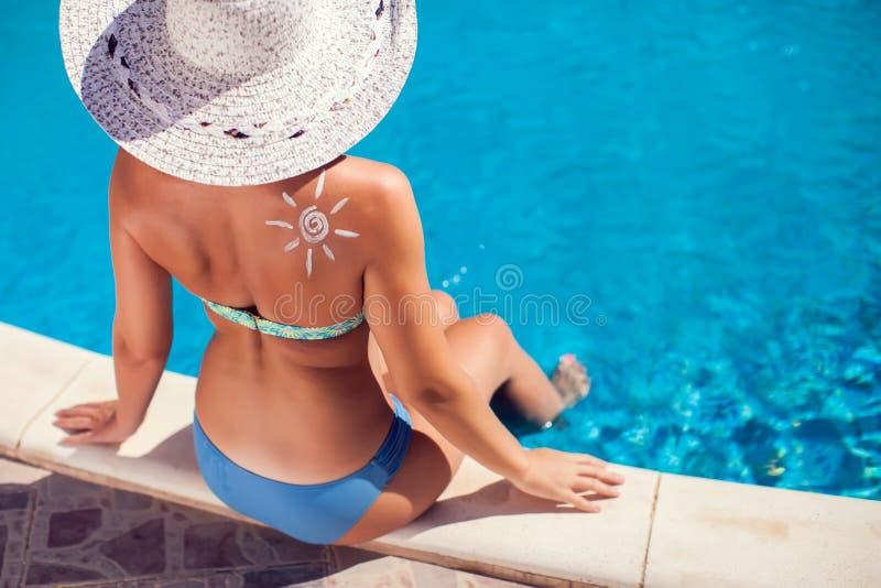 Женщина со сливк предохранения от солнца в форме сердца на ее плече Люди, лето, праздник и концепция здравоохранения стоковое изображение