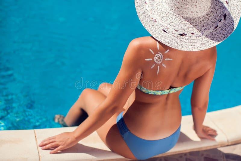 Женщина со сливк предохранения от солнца в форме сердца на ее плече Люди, лето, праздник и концепция здравоохранения стоковая фотография rf