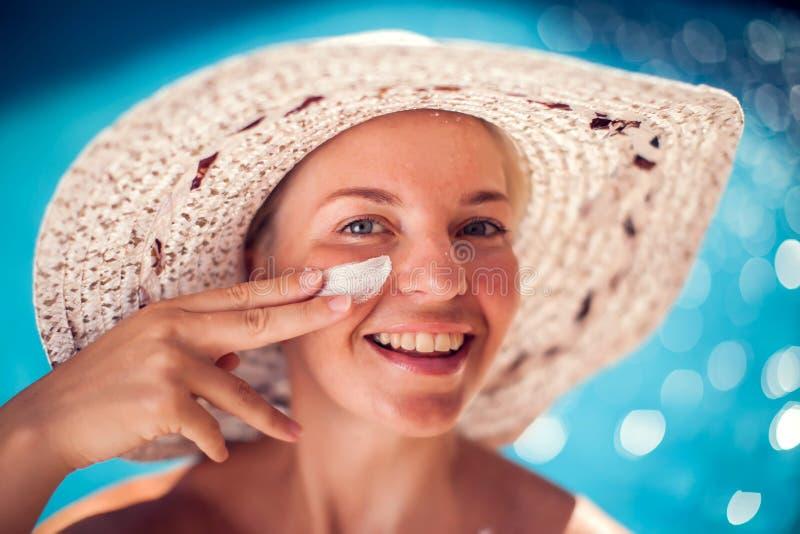Женщина со сливк предохранения от солнца на ее стороне сидя на бассейне Люди, лето, праздник и концепция здравоохранения стоковое изображение rf