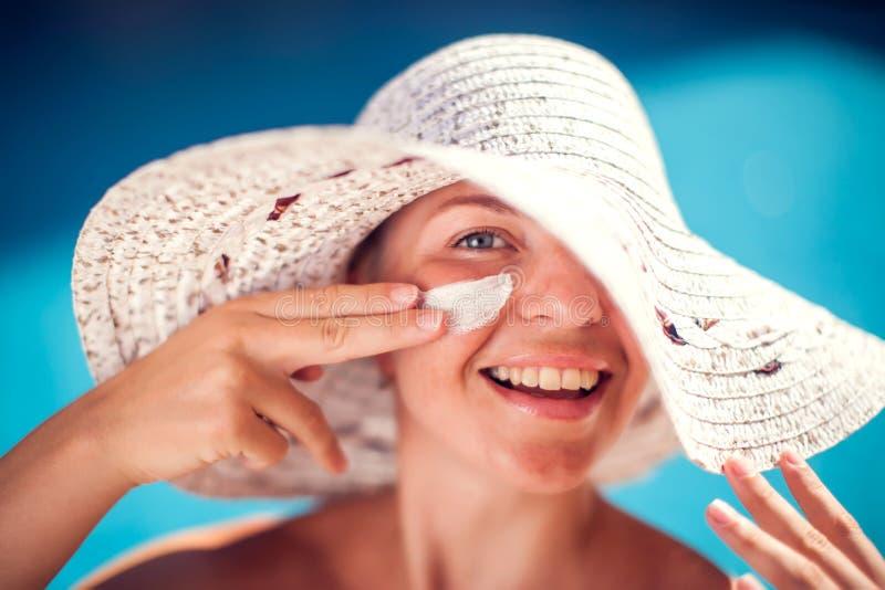 Женщина со сливк предохранения от солнца на ее стороне сидя на бассейне Люди, лето, праздник и концепция здравоохранения стоковые фото