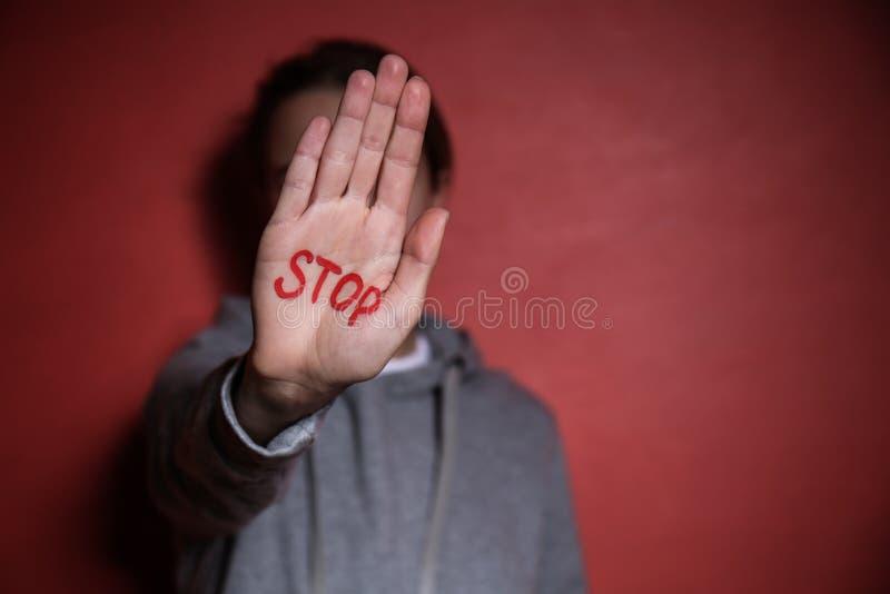 Женщина со словом СТОПОМ написанным на ее ладони против предпосылки цвета Концепция коррупции стоковые изображения