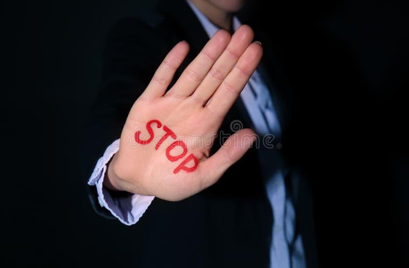 Женщина со словом СТОПОМ написанным на ее ладони против черной предпосылки, крупного плана Концепция коррупции стоковые изображения