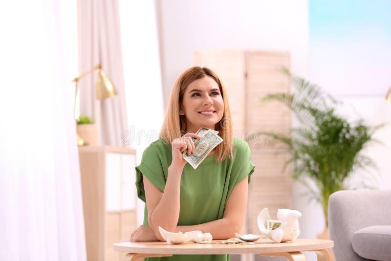 Женщина со сломленными копилкой и деньгами стоковая фотография rf