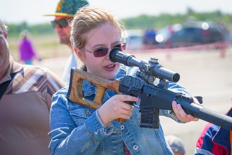 Женщина со стеклами держа снайперскую винтовку с оптически-видимостью стоковое фото