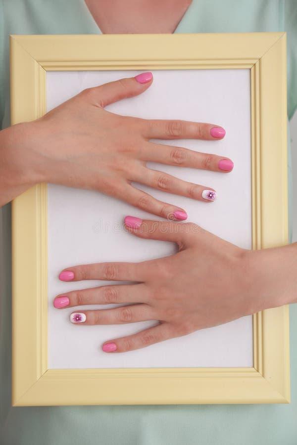 Женщина со стильными ногтями цвета держа пустую рамку фото, крупный план стоковые изображения