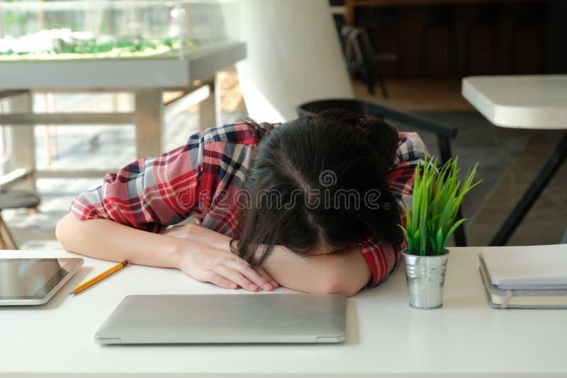 Женщина спать на рабочем месте девушка уставшая от тяжелой работы стоковое изображение