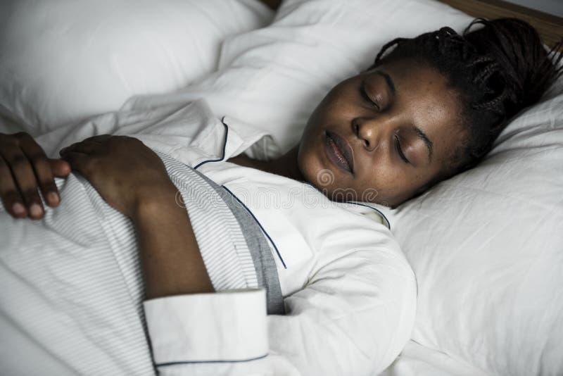 Женщина спать обоснованно на кровати стоковое фото rf