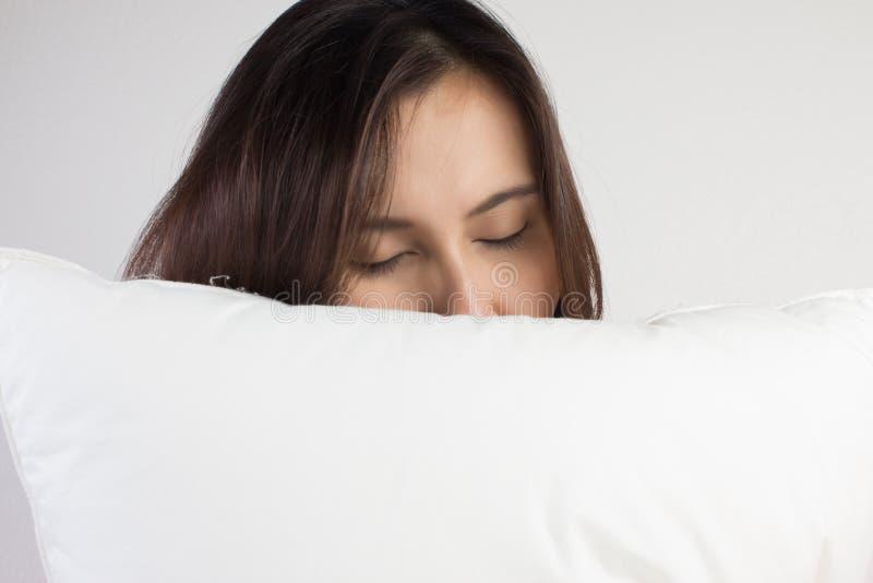 Женщина спать хорошо в кровати обнимая мягкую белую подушку стоковое фото rf