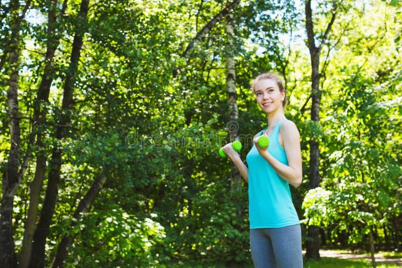 Женщина спорта делая тренировки с гантелями outdoors стоковые фото