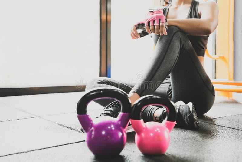Женщина спорта сидя и отдыхая после разминки или тренировки в спортзале фитнеса с встряхиванием протеина или питьевой воде на пол стоковое фото