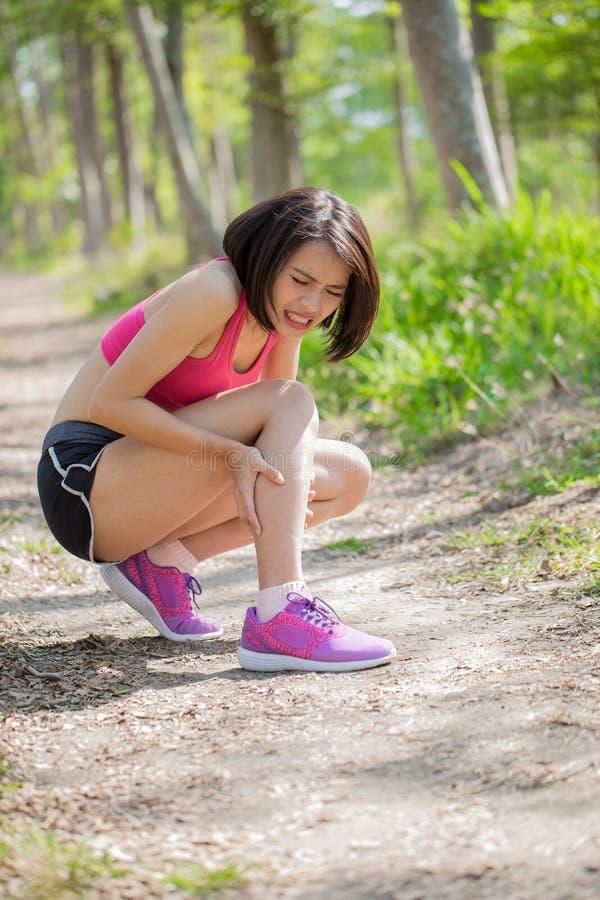 Женщина спорта с напряжением икры стоковая фотография
