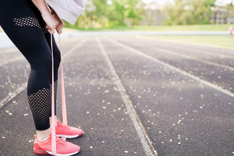 Женщина спорта фитнеса в sportswear моды делая тренировку фитнеса йоги в улице города над серой конкретной предпосылкой r стоковая фотография