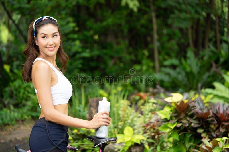 Женщина спорта Smiley молодая держа бутылку воды в парке стоковое изображение