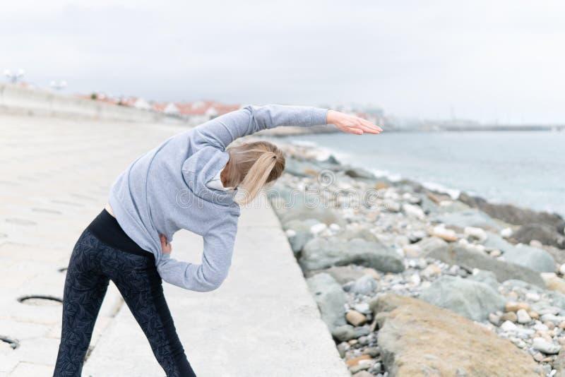 Женщина спортсмена на портовом районе делает тренировки фитнеса стоковое фото rf