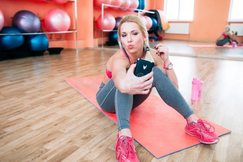 Женщина спортсмена принимая selfie на спортзал стоковые изображения