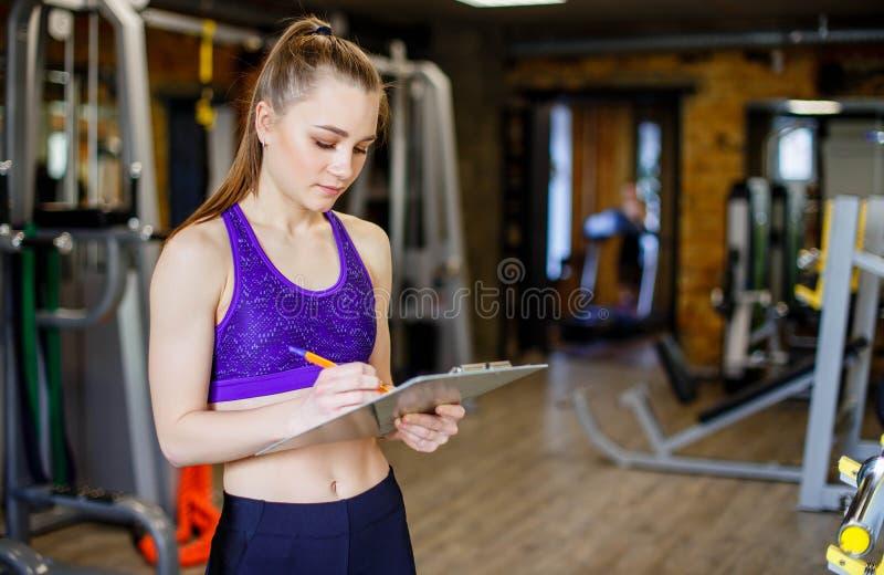 Женщина спорт молодая красивая инструктор в спортзале Тренер спорта школы молодой женщины стоковые изображения