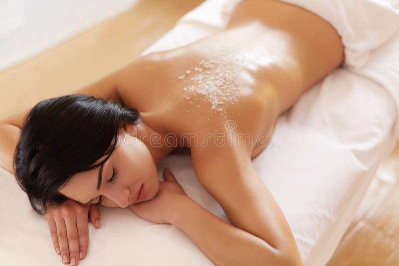 Женщина спы Брюнет получая соль Scrub косметика в стоковые фотографии rf