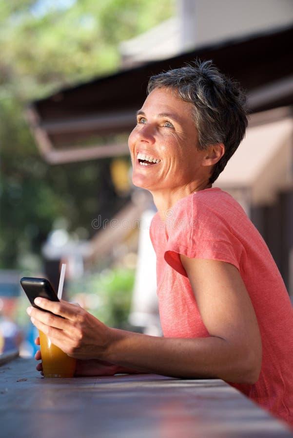 Женщина среднего возраста сидя снаружи с мобильным телефоном и питьем стоковые изображения