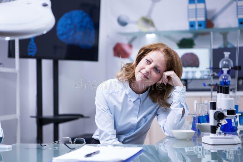 Женщина среднего возраста с красными волосами в биомедицинской лаборатории стоковые изображения