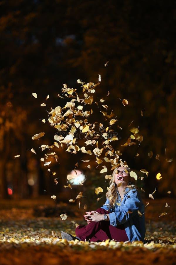 Женщина среди листьев осени стоковые изображения rf