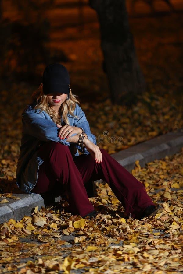 Женщина среди листьев осени стоковые изображения