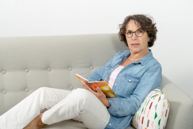 Женщина среднего возраста читает, сидящ на софе стоковые фотографии rf