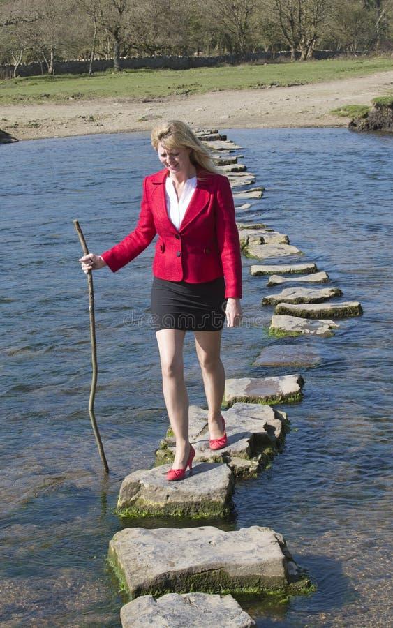 Женщина стартовых площадок идя через реку стоковое фото rf