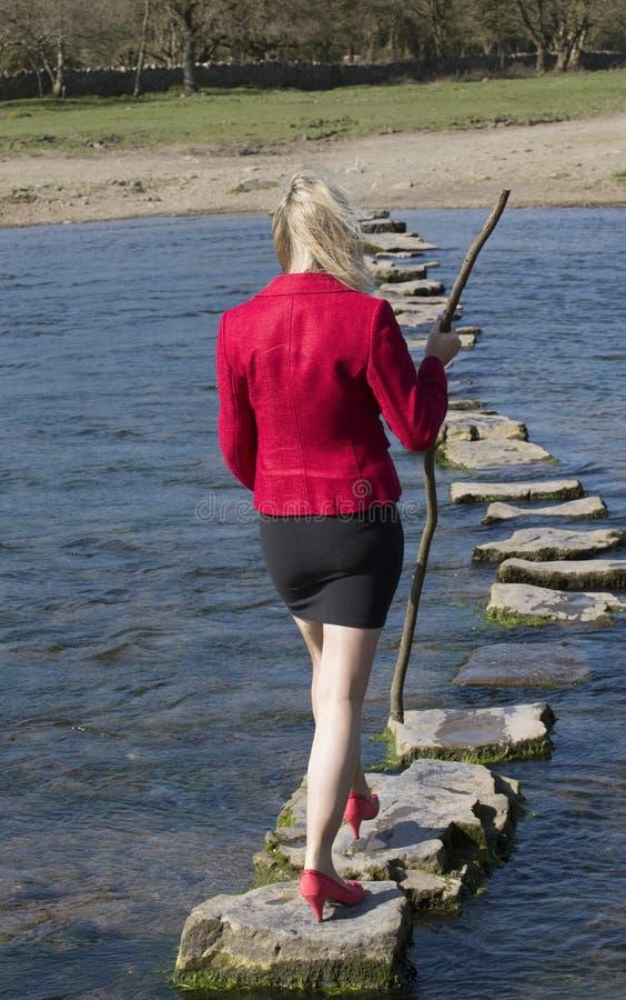 Женщина стартовых площадок идя через реку стоковые фотографии rf