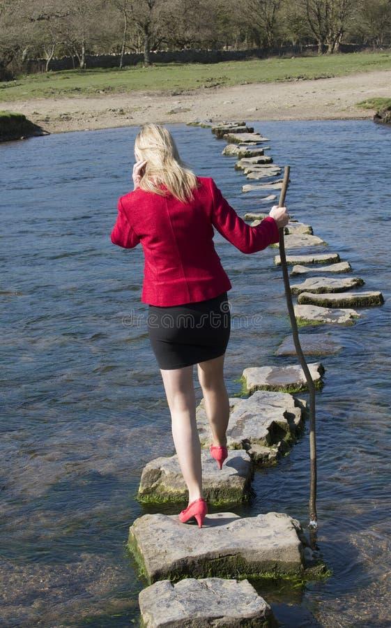 Женщина стартовых площадок идя через реку стоковые изображения