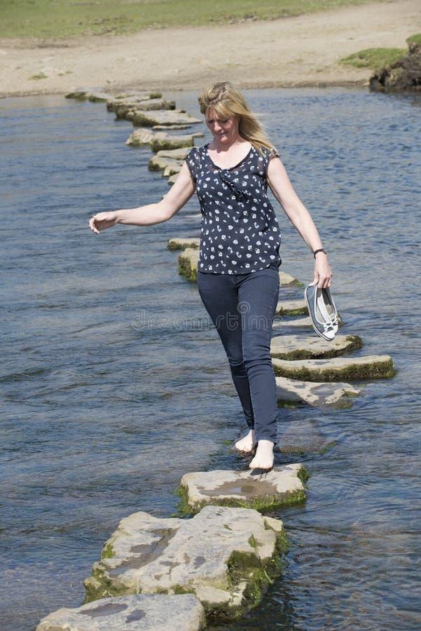 Женщина стартовых площадок barefoot идя через реку стоковые фото