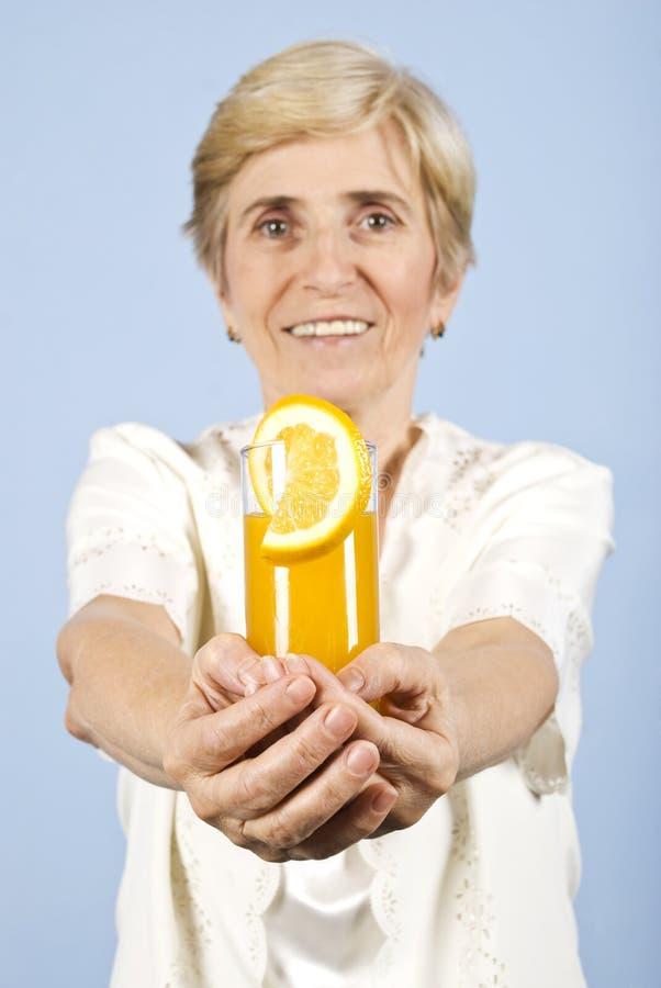 женщина стеклянного счастливого предложения сока померанцовая старшая стоковое фото rf