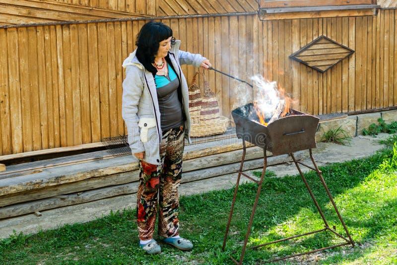 Женщина стоит близко барбекю с горящим швырком и смешивает угли стоковое изображение rf