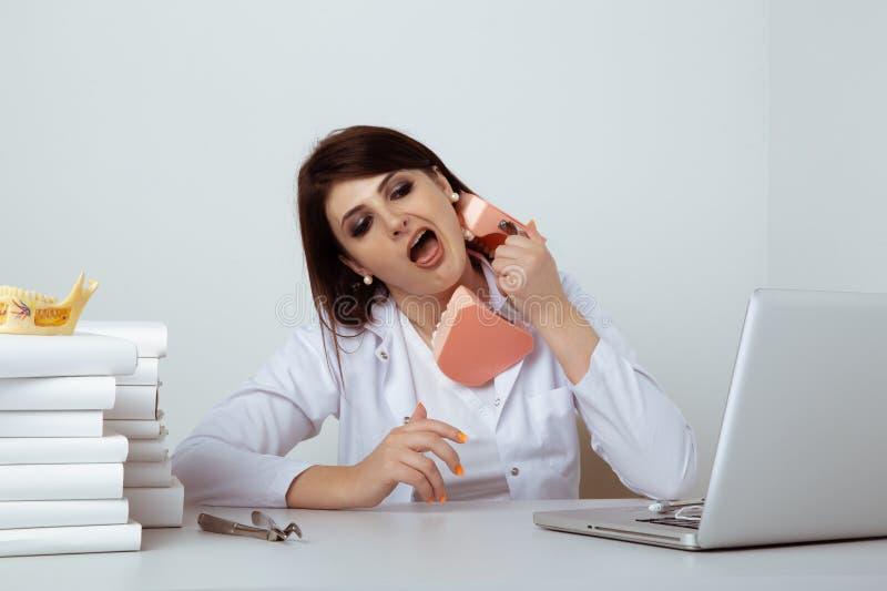 Женщина-стоматолог в офисе, весело играя в модельную челюсть стоковые изображения