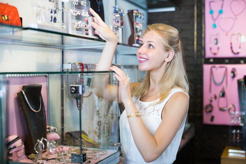 Женщина стоя близко витрина с серьгами стоковое изображение rf