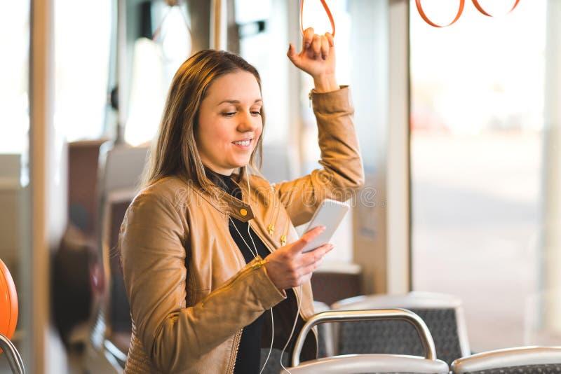 Женщина стоя в поезде, трамвае или шине держа ручку стоковая фотография rf