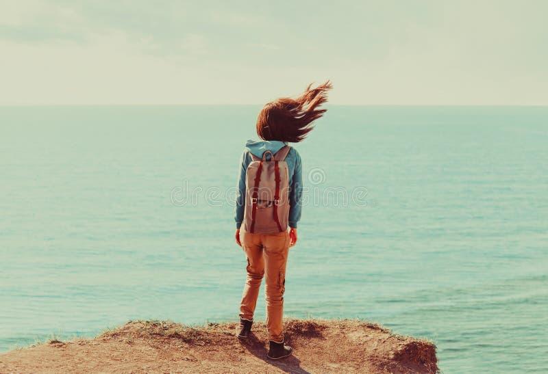 Женщина стоя на береговой линии в ветреной погоде стоковое фото