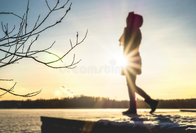 Женщина стоя на пристани озером в зиме на заходе солнца стоковая фотография rf