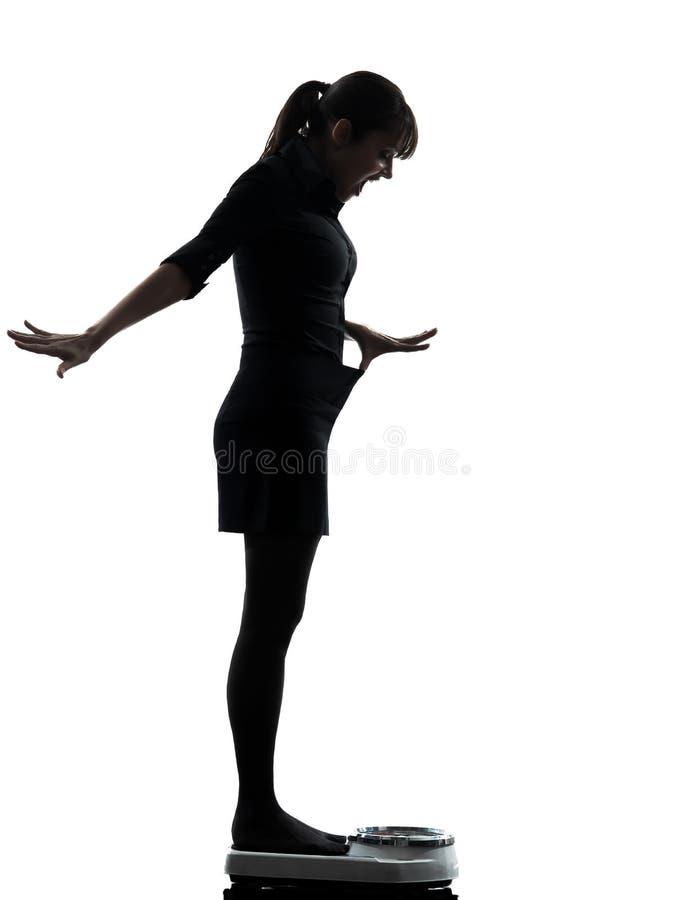 Женщина стоя на силуэте масштаба веса счастливом стоковая фотография