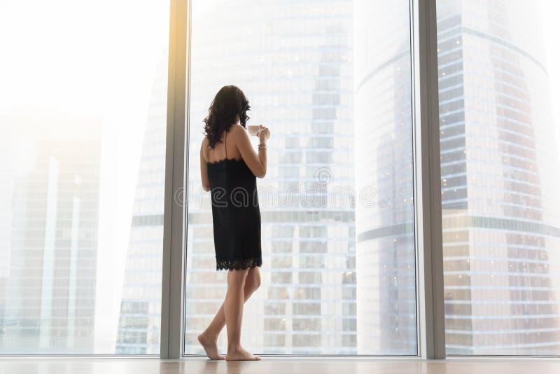 Женщина стоя около окна стоковые фото
