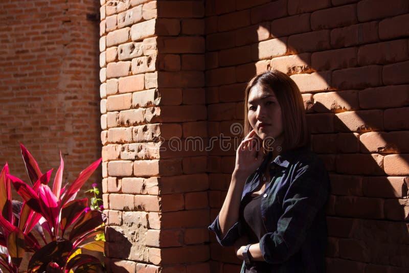 Женщина стоя против стены стоковое фото rf